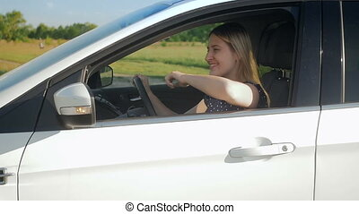 Slow motion video of beautiful smiling young woman driving...