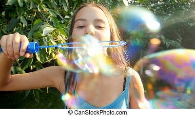 Slow motion video of beautiful teenage girl blowing soap...