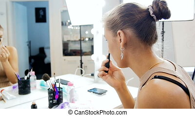Slow motion video of beautiful young female fashion model applying makeup looking in mirror in visage studio