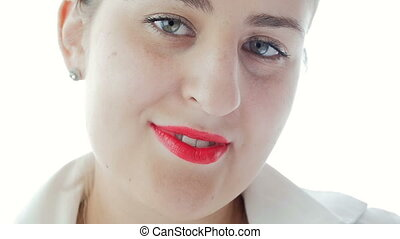 Slow motion video of beautiful young woman in white blouse with red lipstick smiling in camera. Camera defocuses from her face