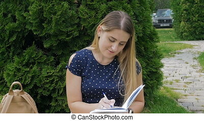 Slow motion video of beautiful young woman sitting with diary on grass at park