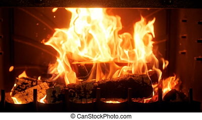 Slow motion video of burning wooden logs in fireplace. ...