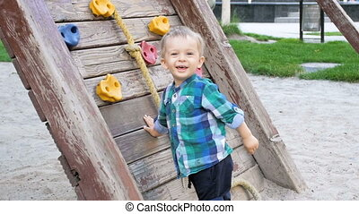 Slow motion video of cheerful smiling toddler boy playing on...