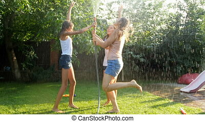 Slow motion video of cheerful teenage girls having fun under...