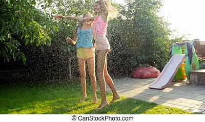 Slow motion video of cheerful teenage girls having fun under...