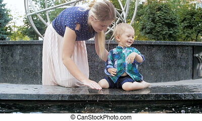 Slow motion video of cheerful toddler boy splashing and playing with young mother in fountain at park