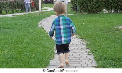 Slow motion video of cute 2 years old barefoot toddler boy...