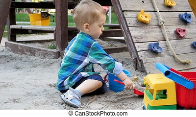 Slow motion video of cute 2 years old toddler boy digging...