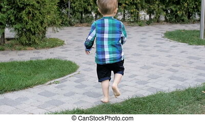 Slow motion video of cute barefoot little boy running on...