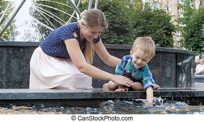 Slow motion video of cute cheerful toddler boy playing and splashing in fountain at park with mother