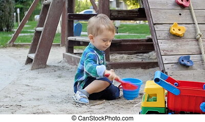 Slow motion video of cute smiling boy plating and digging...