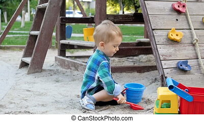 Slow motion video of cute toddler boy digging sand and pouring in plastic bucket on playground at park