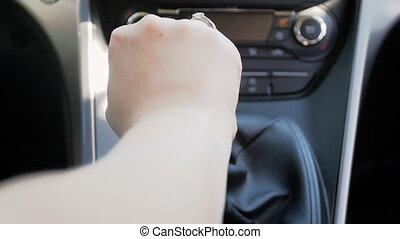 Slow motion video of driver shifting gear box lever on car...