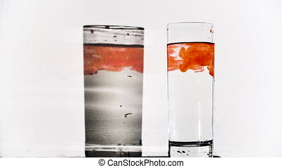 Slow motion video of falling paint's drops in glass with water