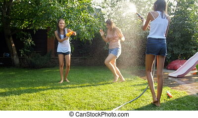 Slow motion video of family having water battle with garden hose and water guns at house backyard