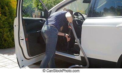 Slow motion video of female driver cleaning her car inside...