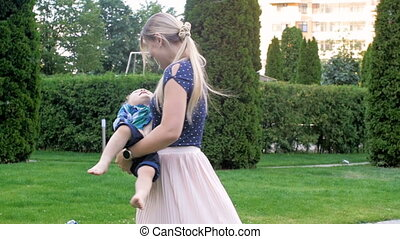 Slow motion video of happy beautiful mother holding and...