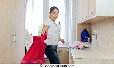Slow motion video of happy cheerful housewife dancing while working in laundry