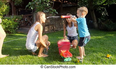 Slow motion video of happy children filling toy water guns...