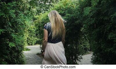Slow motion video of happy elegant woman walking at park...
