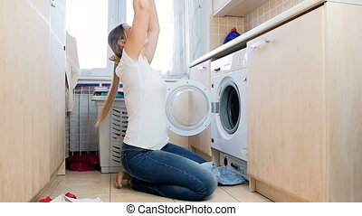 Slow motion video of happy laughing woman taking clothes out of washing machine and throwing in air