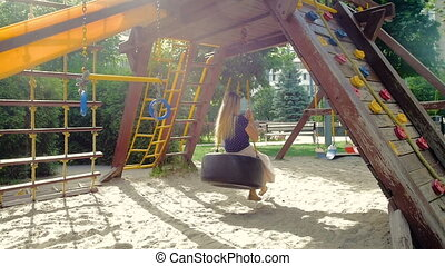 Slow motion video of happy smiling young woman having fun on playground at park