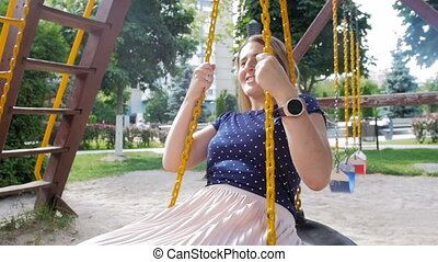 Slow motion video of happy smiling young woman spinning and...