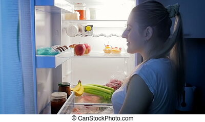 Slow motion video of hungry woman taking apple from refrigerator at night