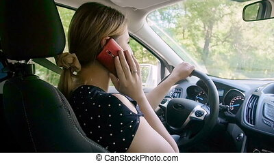 Slow motion video of irresponsible female driver talking by...