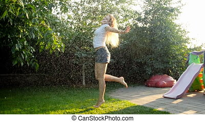 Slow motion video of laughing young woman dancing and jumping under water from garden sprinkler at sunset