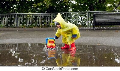 Slow motion video of little toddler boy in rubber boots and ...