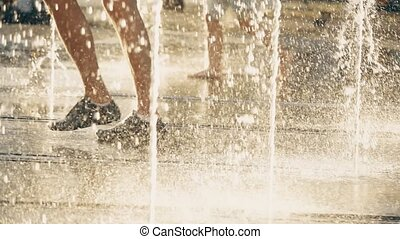 Slow motion video of people walking in fountain on a summer...