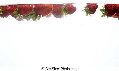 Slow motion video of raspberries floating in water against white background