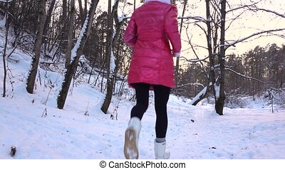 Slow motion video of slim girl in red jacket running from the camera in winter forest