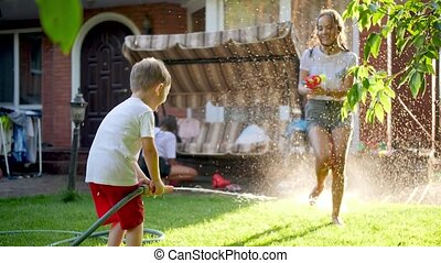 Slow motion video of teenage girl having water battle with little boy using garden hose and water gun