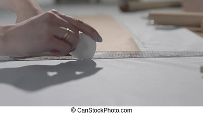 Slow motion video of the fashion designer that works at the table with curves and a pattern, draws a soap slice, around lies scissors, centimeter, a notebook with sketch, sew studio, top view