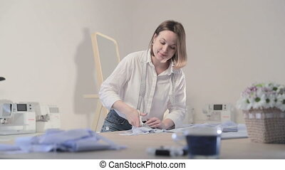 Slow motion video of the fashion designer which works at a table with curves and a pattern, she are cutting fabric, around lies scissors, centimeter, sew machine and dummy on the background