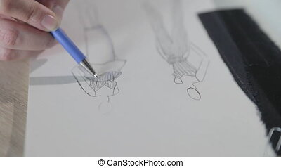 Slow motion video of the girl draws the sketch of future model of clothes in the notebook, tools for sewing, sewing agency, a bunch of flowers, paper craft