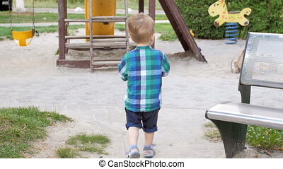 Slow motion video of toddler boy running and throwing ball...