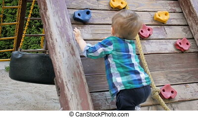 Slow motion video of toddler boy trying to climb on wooden...