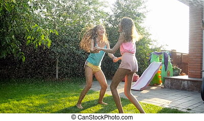 Slow motion video of two cheerful girls dancing and jumping...