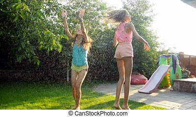 Slow motion video of two cheerful girls having fun under...