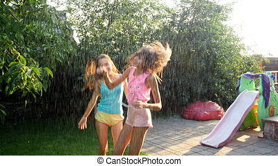 Slow motion video of two cheerful teenage girls dancing under the summer rain in sunset light