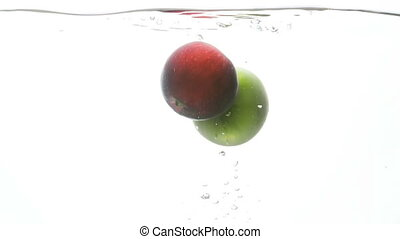 Slow motion video of two fresh red and green apples falling and splashing in cold water against white background