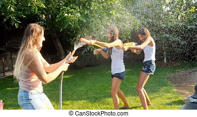 Slow motion video of two laughing girls having water gun battle with mother on grass at backyard