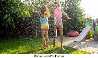 Slow motion video of two laughing teenage girl enjoying summer rain on grass at backyard