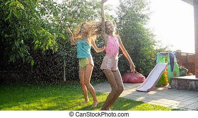 Slow motion video of two laughing teenage girls jumping and dancing under summer rain at sunset
