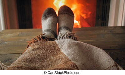 Slow motion video of woman lying under plaid at fireplace...