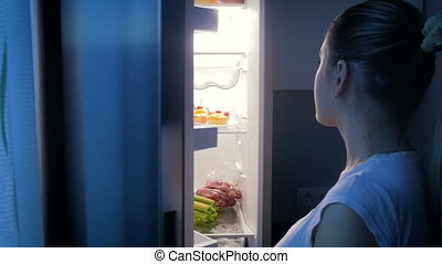 Slow motion video of woman opens refrigerato at night and...