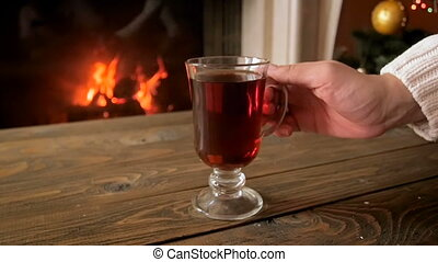Slow motion video of woman relaxing by the fireplace on Christmas and drinking tea